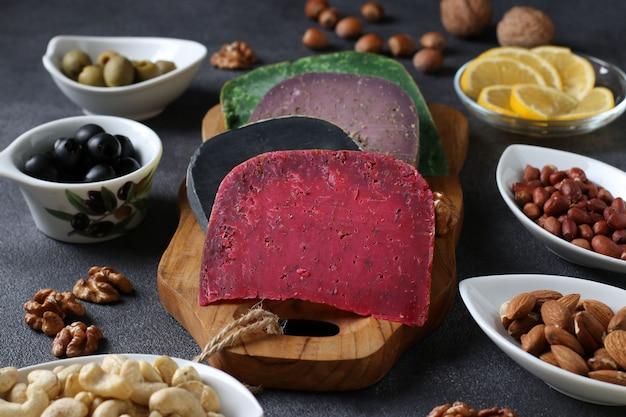 다양한 색상의 미식가 치즈, 올리브, 견과류, 슬라이스 레몬. 와인 파티 간식. 확대 프리미엄 사진
