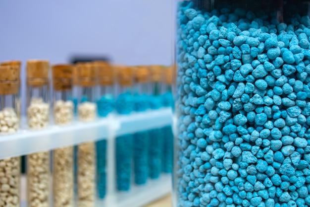 Разноцветные гранулы микронутриентных удобрений в пробирках в ряд