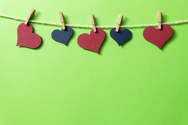 Multi-colored hearts with a rope on tiny clothespins hang on a green background.