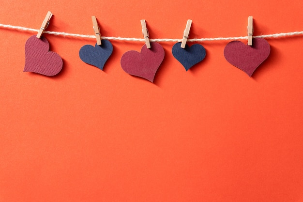 Multi-colored hearts with a rope on tiny clothespins hang on a red background.