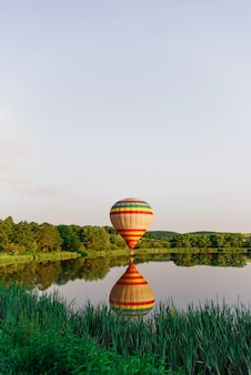 Multi colored hot air balloon flying above lake close to water. ballooning in nature.