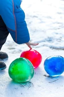 Разноцветные ледяные шары в снегу в солнечный зимний день