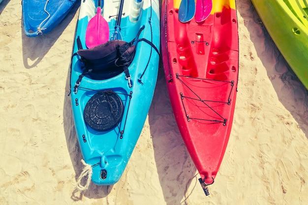 Разноцветные каяки с веслами на песке у моря вид сверху