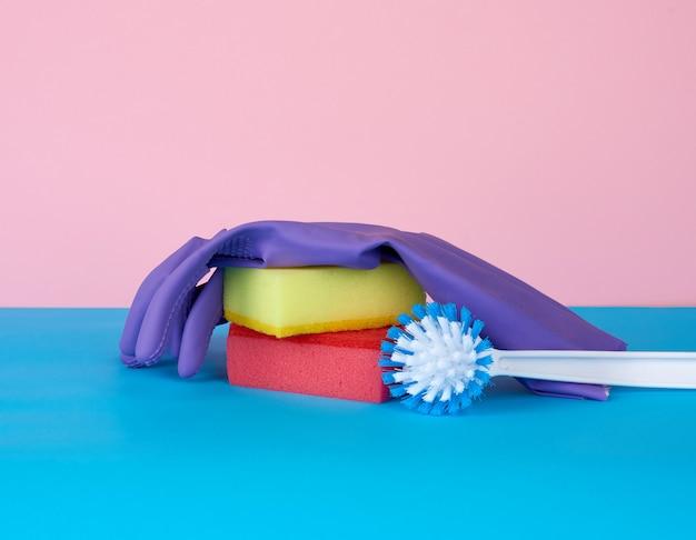 Multi-colored kitchen sponge, white plastic brush, rubber purple gloves