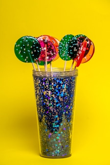 Multi-colored lollipops in a blue glass on a yellow background.