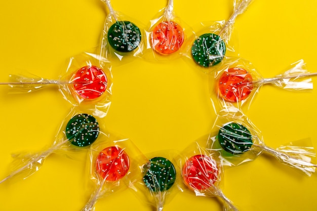 Multi-colored lollipops on a stick on a yellow background.