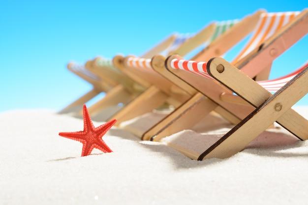 色とりどりのラウンジチェアが一列に並び、ヒトデが砂浜にクローズアップ。コピースペースのある空