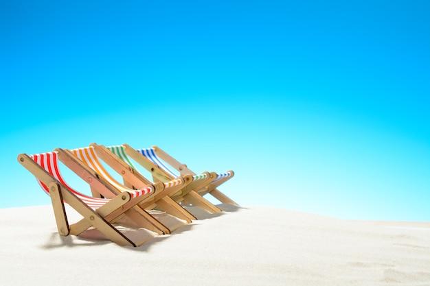 砂浜に並んだマルチカラーのラウンジチェア。コピースペースのある空