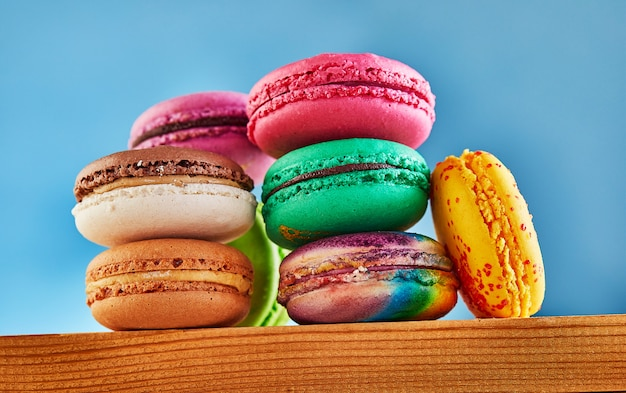 Multi-colored macarons folded in a stack on a wooden surface