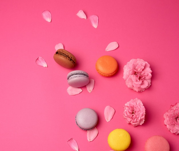 Multi-colored macarons with cream and a pink rose bud with scattered petals