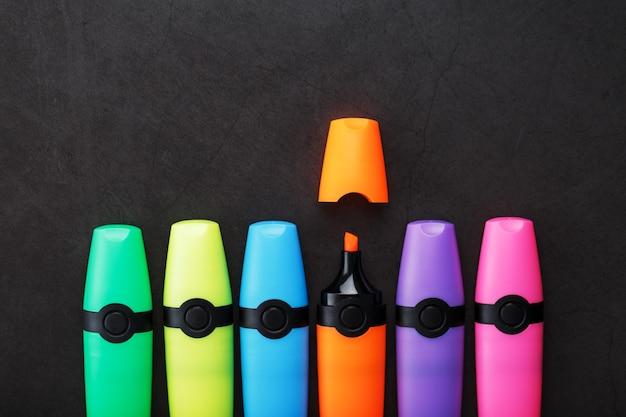 Разноцветные маркеры в ряд на черном фоне, вид сверху. понятие творчества и времени учебы