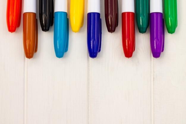 Разноцветные маркеры на белом деревянном фоне. вид сверху. скопируйте пространство.