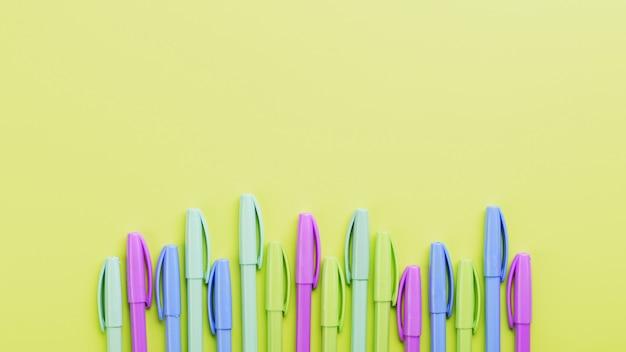 Разноцветные маркеры на желтом со свободным пространством.
