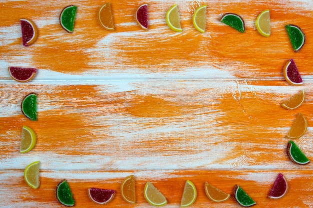 Multi-colored marmalade in the form of citrus slices laid out as a frame on an orange board