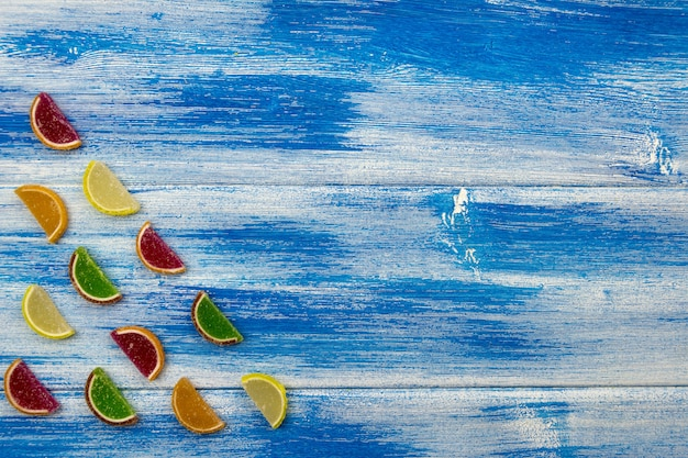 Multi-colored marmalade in the form of citrus slices laid out in a corner on a blue board