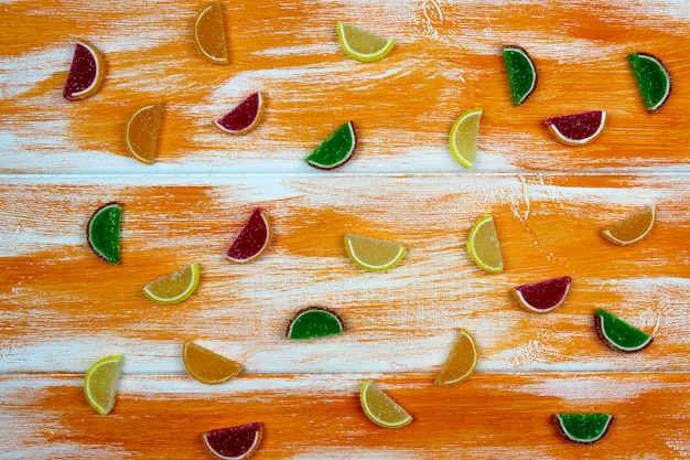 Multi-colored marmalade in the form of citrus slices scattered on an orange board