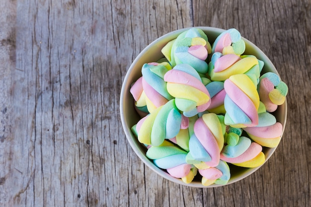 Multi-colored marshmallow twist in a bowl on a wooden table.
