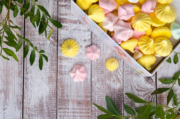 Multi-colored meringue in a gift box on wooden vintage background.
