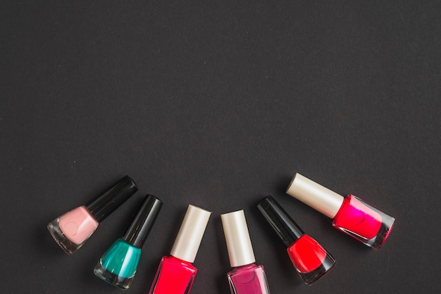 Multi colored nail polish bottles forming curve shape on black background