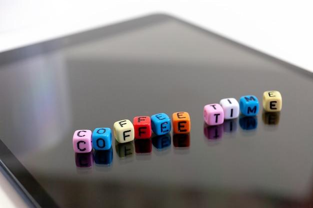 Пестротканый блоков кубов писем с концепциями времени кофе на экране таблетки.