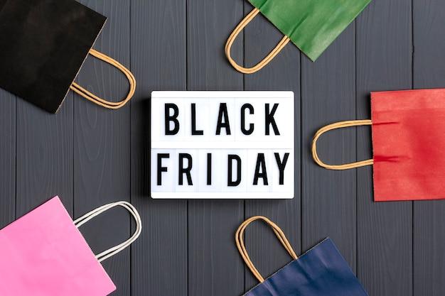 멀티 컬러 포장 봉투, 어두운 회색 표면에 검은 금요일 텍스트가있는 선물 상자 라이트 박스 평면 배치
