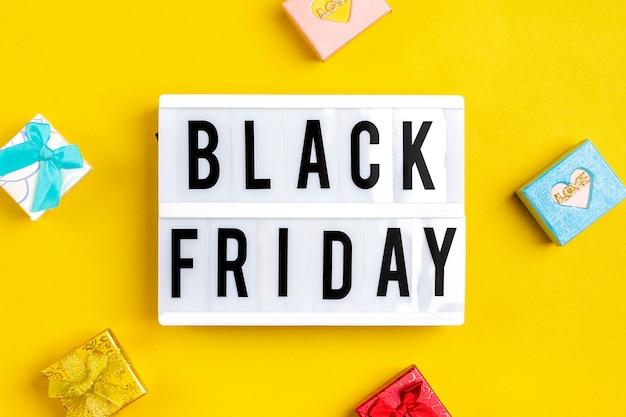 Multi - colored packaging bags, gift boxes lightbox with text black friday on  yellow background