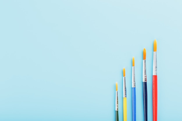 Multi-colored paint brushes on a blue background.