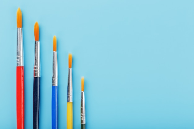 Multi-colored paintbrushes on a blue background.