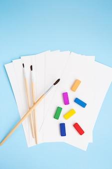 Разноцветные краски, акварельные кисти разных размеров лежат вместе с акварельной бумагой на синем фоне. уроки рисования. вид сверху.