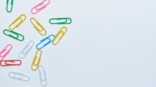 Multi-colored paper clips on a white background.