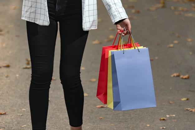 Разноцветные бумажные хозяйственные сумки в женской руке. продажа и покупки.
