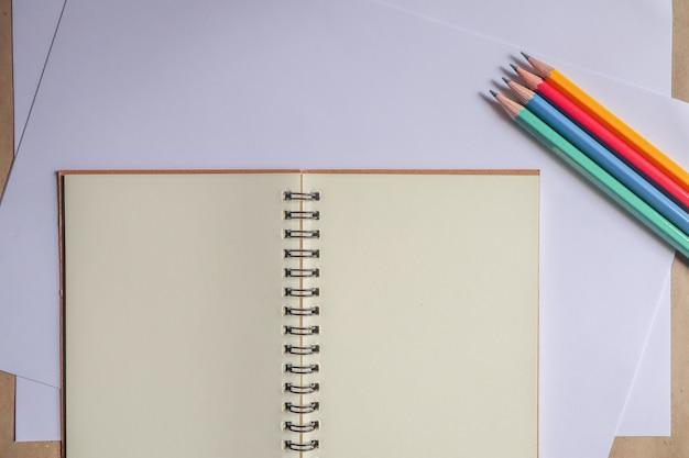 マルチカラーの鉛筆と茶色のノート