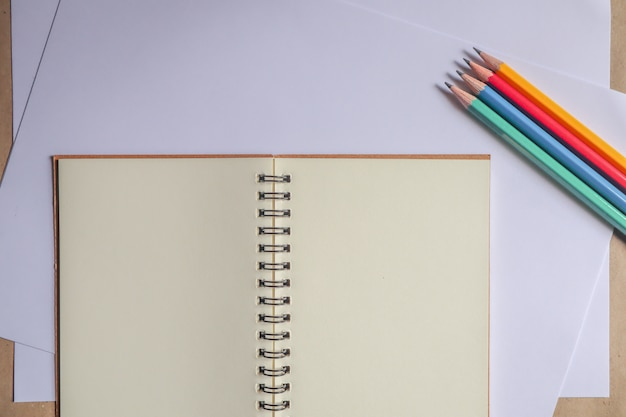 Multi-colored pencils and brown notebooks