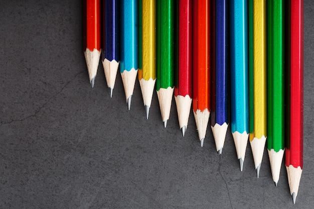 Разноцветные карандаши для рисования и рисования подряд на фактурном черном фоне подряд