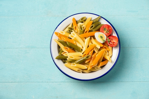 Multi-colored penne pasta in a plate on a blue background.