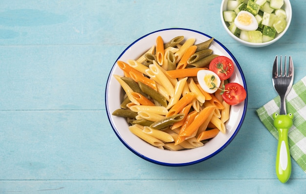 Multi-colored penne pasta in a plate on blue