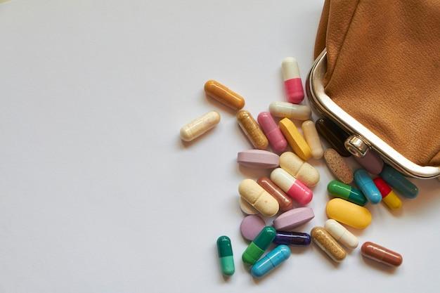 Разноцветные таблетки и капсулы выливаются из маленького кошелька, медицинская концепция для борьбы с пандемией коронавируса