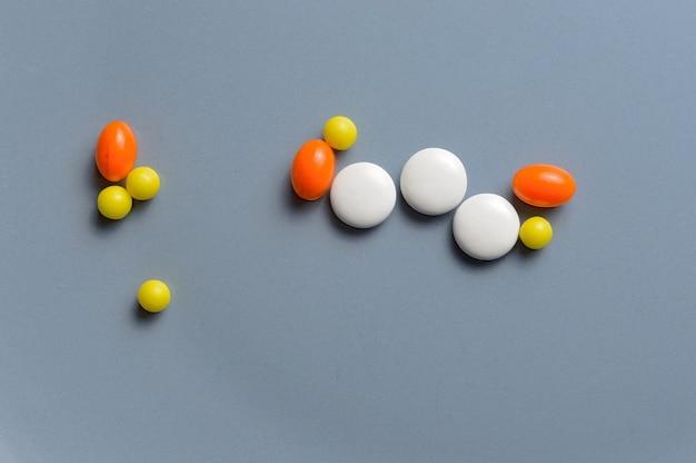 灰色の背景のカプセルのマルチカラーの丸薬とビタミン。上面図