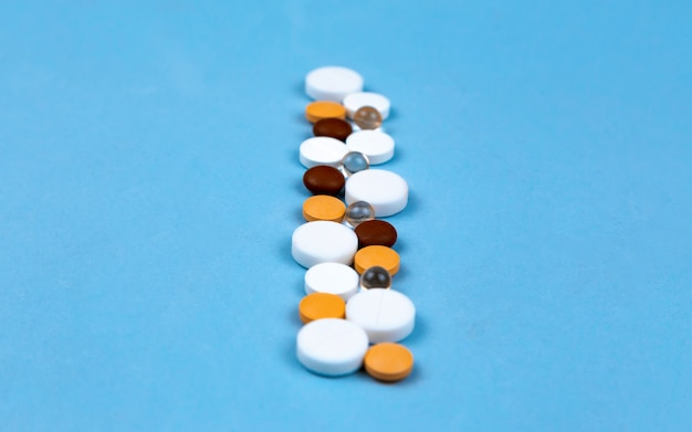 Multi-colored pills and capsules are laid out on a blue background in a row