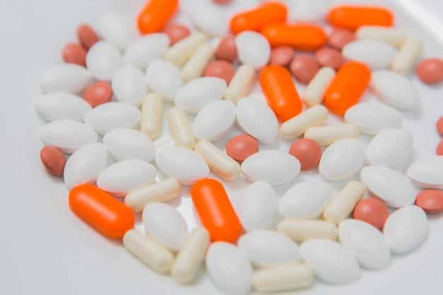 Multi-colored pills in a white plate