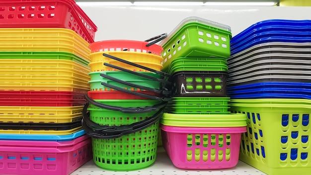 Разноцветные пластиковые контейнеры разных форм и размеров с крышками и без, сложенные стопкой на витрине магазина. продажа ящиков для хранения и уборки. современная кухонная утварь.