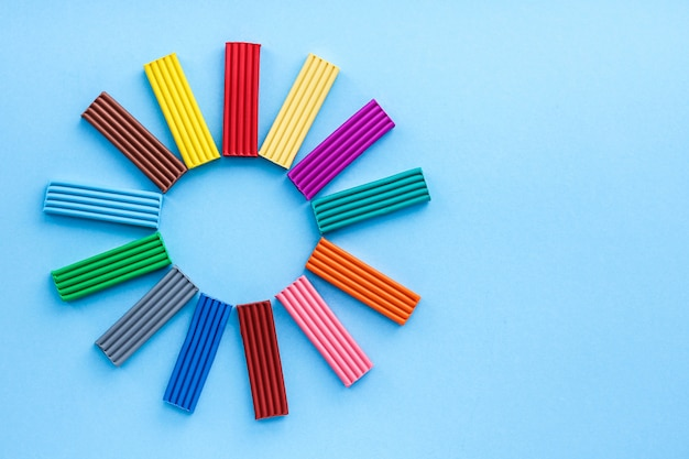 色とりどりの塑像用粘土は、子供たちと一緒に創造力を発揮する素材です。モデリング-細かい運動能力の発達。青色の背景に、トップビュー。
