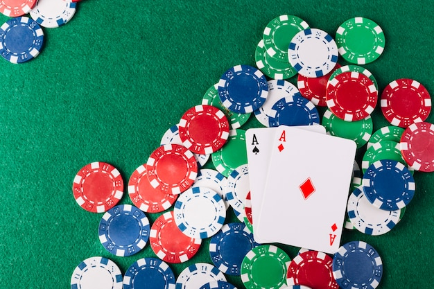 Multi colored poker chips and two aces playing cards on green background