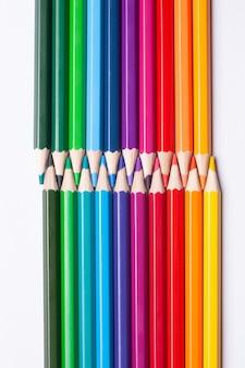 Разноцветные радужные карандаши взаимодействуют с острыми концами, изолированными на белом фоне.