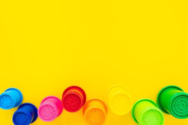 노란색 배경에 모래에 대한 여러 가지 빛깔의 무지개 모양. 밝은 아기 배경, 평평한 위치, 위쪽 보기, 텍스트 복사 공간. 어린이 장난감의 구성.