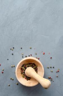 木製の乳鉢でマルチカラーの赤、緑、黒のコショウの実