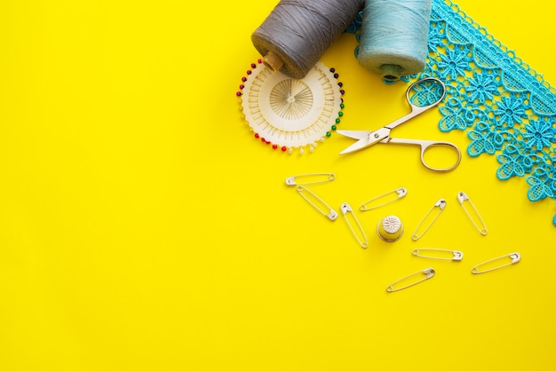 Multi-colored reels with sewing threads, meter tape, scissors on a bright background. flat lay