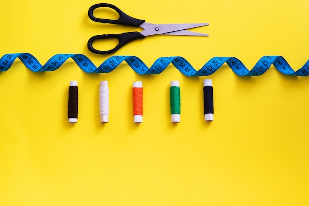 Multi-colored reels with sewing threads, meter tape, scissors on a bright background