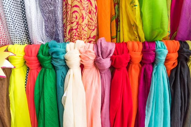 The multi-colored  scarves  hanging  on a wooden  hanger.