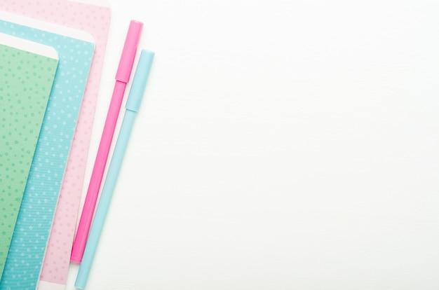 マルチカラーの学校の子供たちのノートと白い木製の背景、学校の机の上のペン。コピースペース、平面図、フラットレイアウト。